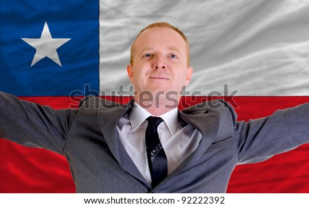 joyful investor spreading arms after good business investment in chile, in front of flag