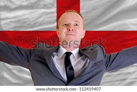 joyful investor spreading arms after good business investment in england, in front of flag