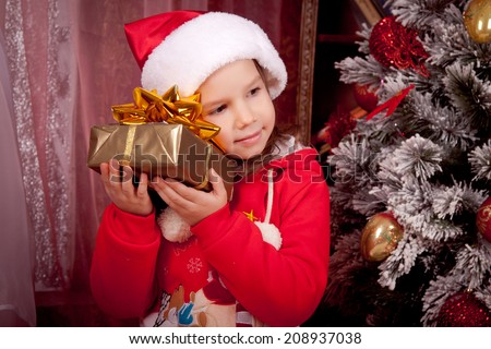 Joyful kid dressed as Santa put his ear to the present, Christmas, New Year - stock photo