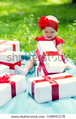Joyful kid girl with colorful gift boxes playing in park - stock photo