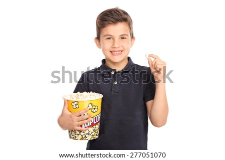 Joyful kid holding a big box of popcorn and looking at the camera isolated on white background - stock photo