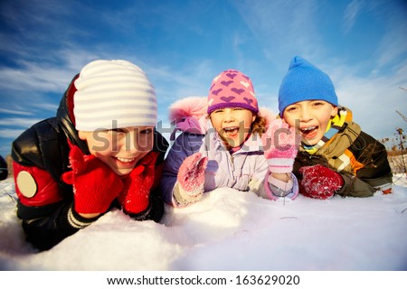 Joyful kids in winterwear lying in snowdrift and laughing - stock photo