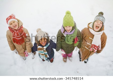 Joyful kids standing in snowdrift and looking at camera - stock photo