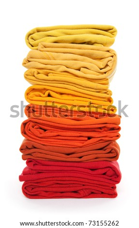 Joyful laundry. Pile of red and yellow folded clothes on white background. - stock photo