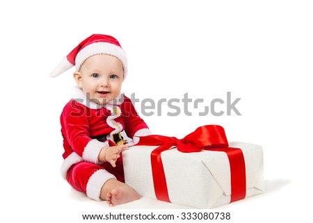 joyful little baby dressed as Santa Claus with a big Christmas present in a box - stock photo