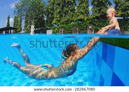Joyful little baby having a fun and laughing with diving mother in swimming pool with blue water during summer family vacation with child in a tropical resort,  underwater portrait - stock photo