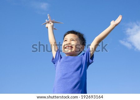 joyful little boy holding a toy with blue sky background - stock photo