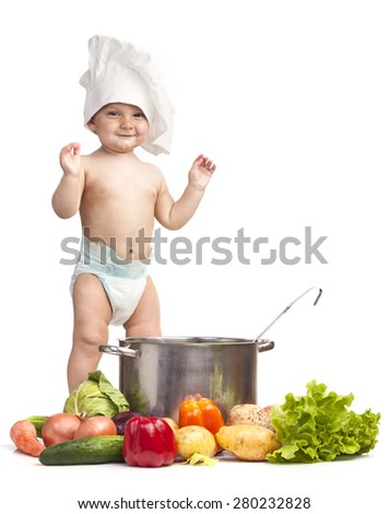 Joyful little boy in chef's hat playing with casserole and vegetables - stock photo