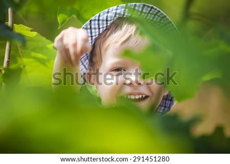 Joyful little boy in summer park - stock photo