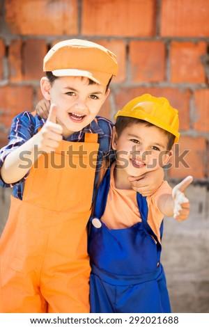 Joyful little builders in helmet on a building site - stock photo