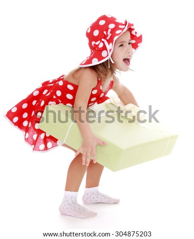 Joyful little girl in a red summer dress with polka dots and red hat holding hands huge box with a gift-Isolated on white background