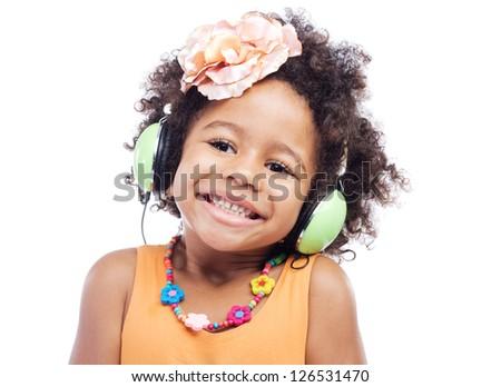Joyful little girl in big headphones against white background - stock photo