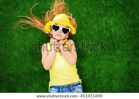 Joyful little girl in colorful clothes and sunglasses lying on a green lawn. Kid's fashion. Summer holidays. - stock photo