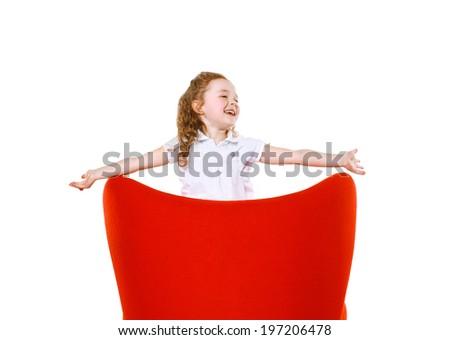 Joyful little girl in red chair - stock photo