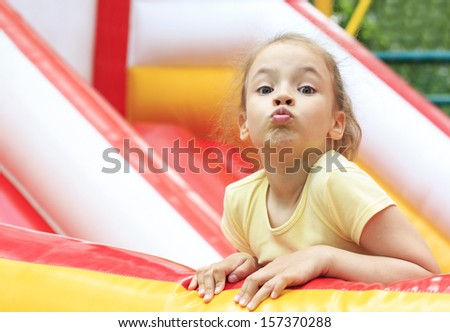 Joyful little girl makes a face on a trampoline.