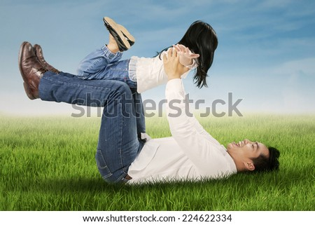 Joyful little girl playing with her father on the meadow enjoy summer time - stock photo