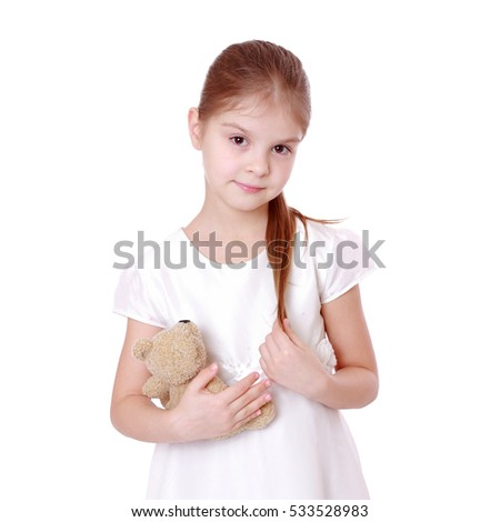 Joyful little girl playing with teddy bear