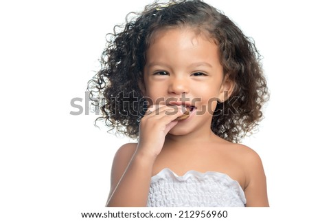 Joyful little girl with an afro hairstyle eating a chocolate cookie isolated on white - stock photo