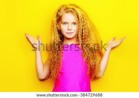Joyful little girl with beautiful blonde hair over yellow background. Kid's style. Hairstyle. - stock photo
