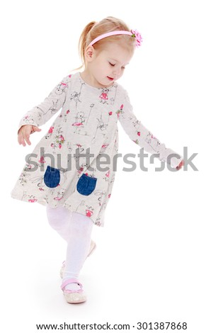 Joyful little girl with blond hair and a rim in the form of roses on his head running around the room waving his arms. Girl playing salochki her friends. On the girl wearing a long dress and a bright - stock photo