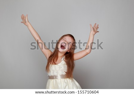 Joyful little girl with long hair dancing and laughing on a gray background - stock photo