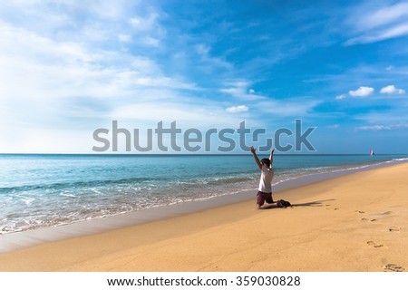 joyful lonely guy is on his knees on a beautiful deserted beach and looking into the distance over the sea and waving his arms