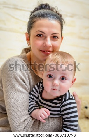 Joyful loving young mother with her baby clasped closed to her chest in her arms looking at the camera with a beaming smile of happiness