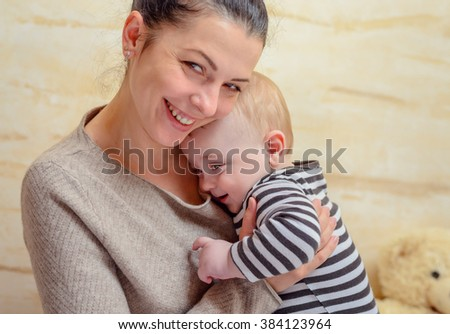 Joyful loving young mother with her baby clasped closed to her chest in her arms looking at the camera with a beaming smile of happiness - stock photo