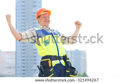 Joyful male construction worker. He raised his hands up in delight. They completed the construction. Happy contractor at a building site. Male construction worker at a building site smiling.