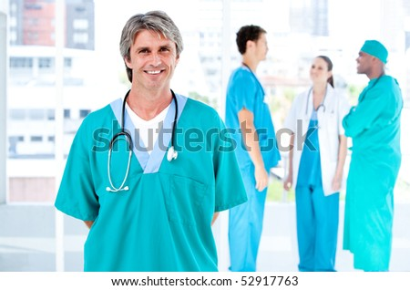 Joyful male doctor looking at the camera while his medical partners talking together in the hospital