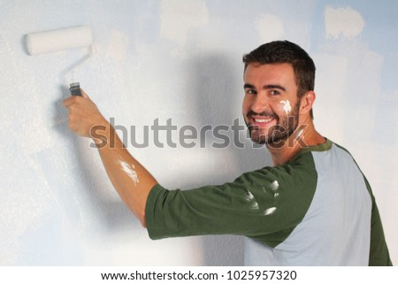 Joyful male painting a wall with a roller and smiling
