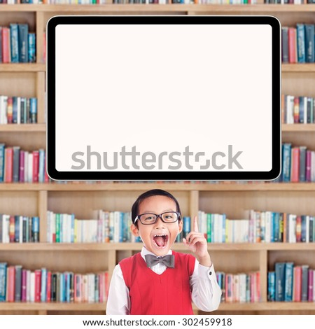 Joyful male primary school student pointing at a blank whiteboard in the library - stock photo