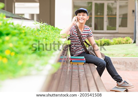 Joyful male student sitting on the bench and talking on the phone - stock photo