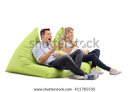 Joyful man and woman eating popcorn seated on beanbags and watching something isolated on white background - stock photo