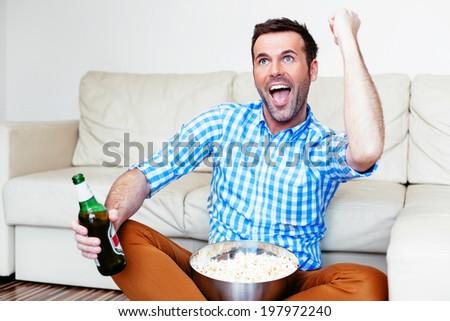 Joyful man enjoying the victory moment of his team on tv - stock photo