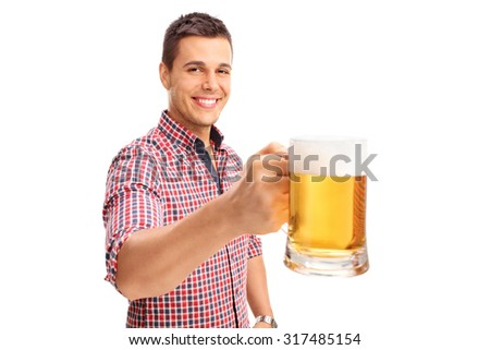 Joyful man holding a large beer mug full of beer and looking at the camera isolated on white background - stock photo