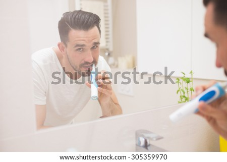 Joyful man looking at camera in mirror reflection during brushing teeth with an electric toothbrush - stock photo