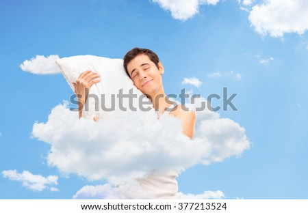 Joyful man sleeping and hugging a soft pillow up in clouds in the sky - stock photo