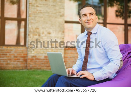 Joyful man using laptop outdoors - stock photo