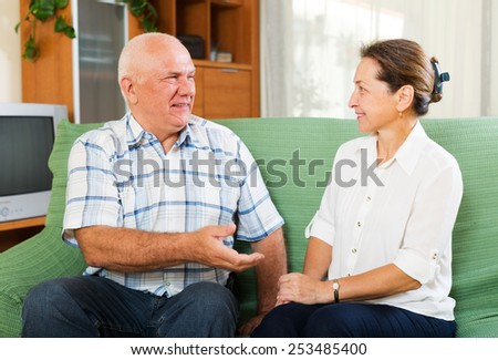 joyful mature couple gossiping together   at home