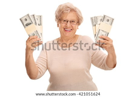 Joyful mature woman holding stacks of money and looking at the camera isolated on white background - stock photo
