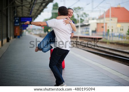 Joyful meeting at the railway station. The young man easily lifted the girl. She hugged him tightly. On a girl's face happy smile.