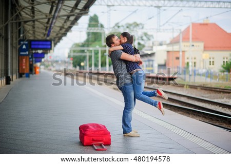 Joyful meeting at the railway station. The young man lifted the girl. Couple hugging and kissing. Nearby the red suitcase has fallen.