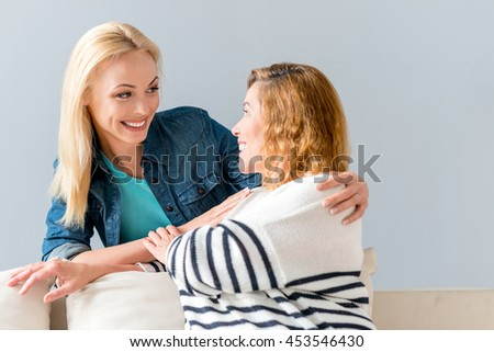 Joyful mom and daughter hugging happily - stock photo