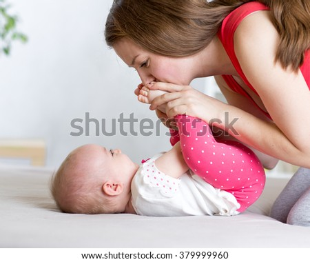 joyful mom playing with her baby infant