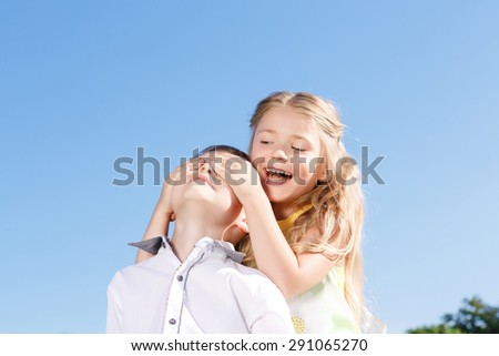 Joyful moment. Pretty little girl holding her hands on the face of boy and closing his eyes while sitting on blanket alfresco - stock photo