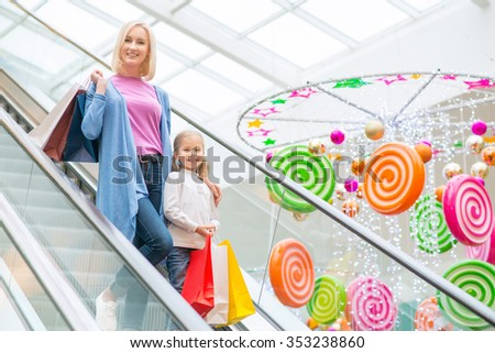 Joyful mood.  Cheerful smiling mother and daughter standing on escalator and holding packages while having shopping