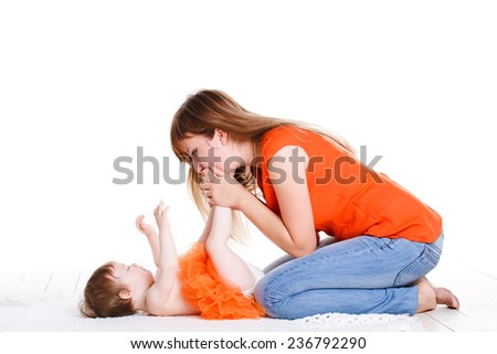 joyful mother playing with her baby infant. young mum and the kid on a white. joyful mother playing with her baby infant. joyful mother playing with her baby infant - stock photo