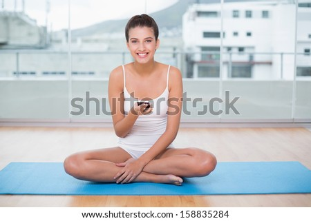Joyful natural brown haired woman in white sportswear texting with her mobile phone in bright living room