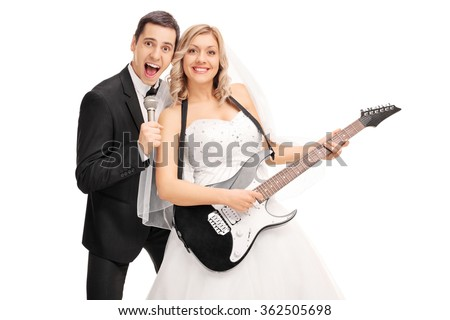 Joyful newlywed couple having fun and playing music isolated on white background - stock photo